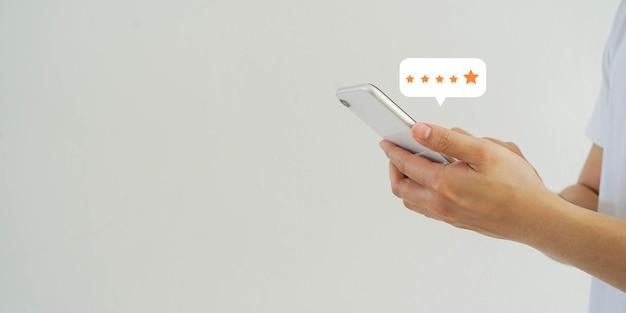 Man hand te drukken op smartphone scherm met gouden vijfsterrenbeoordeling feedback