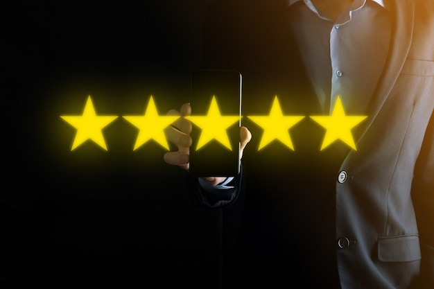 Man hand tonen op vijf sterren uitstekende rating. vijf sterrensymbool aanwijzen om de rating van het bedrijf te verhogen. review, rating of ranking, evaluatie en classificatie concept verhogen.