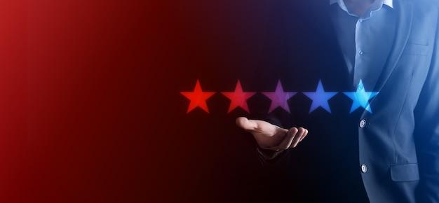 Man hand tonen op vijf sterren uitstekende rating. wijzend vijf sterren symbool om de waardering van het bedrijf te verhogen. review, rating of ranking, evaluatie en classificatie concept te verhogen