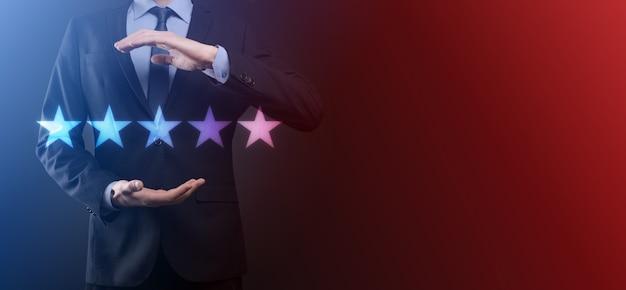 Man hand tonen op vijf sterren uitstekende rating. wijzend vijf sterren symbool om de waardering van het bedrijf te verhogen. review, rating of ranking, evaluatie en classificatie concept te verhogen.