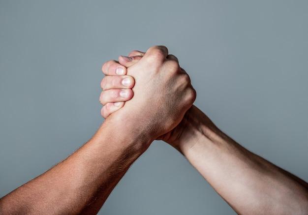Man hand. twee mannen armworstelen. armen worstelen. dichtbij. vriendelijke handdruk, groeten van vrienden, teamwerk, vriendschap. handdruk, armen