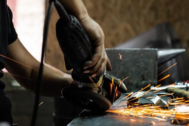 Man handen behandelen van metalen onderdelen van hardware in een workshop met haakse slijper. mannelijke metaalbewerker polijsten en finaliseren stuk middeleeuws pantserkostuum.