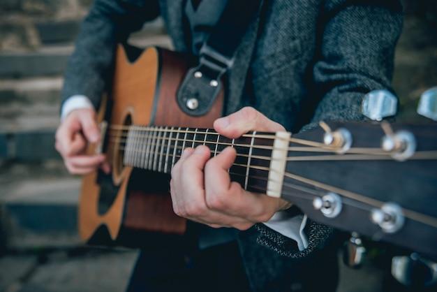Man handen die akoestische gitaar spelen. authentieke achtergrond.