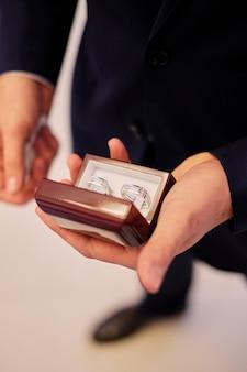 Man handen die een witte doos met trouwringen houden