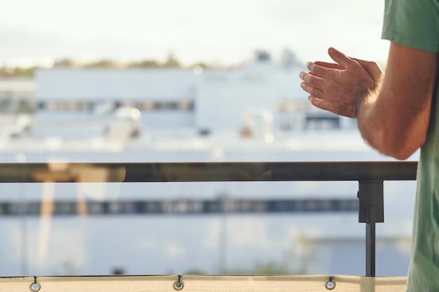 Man handen die het raam verpletteren op een zonnige dag tijdens de isolatie van spanje door het coronavirus, gezien door een ruit