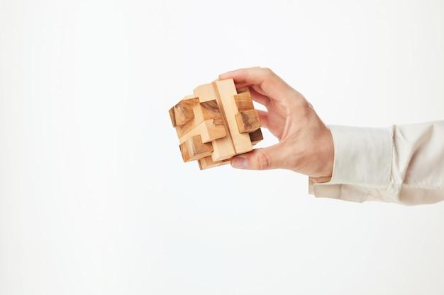 Man handen die houten raadsel houden.