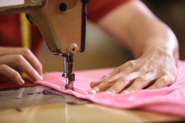 Man handen die op een sewinghine naaien bij een kledingsfabriek