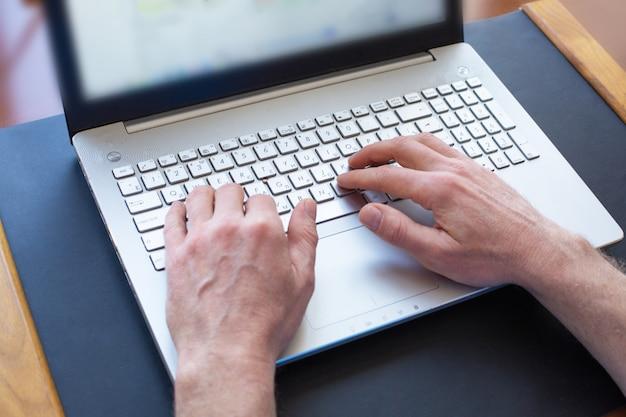 Man handen die op laptop toetsenbord bij het bureau typen