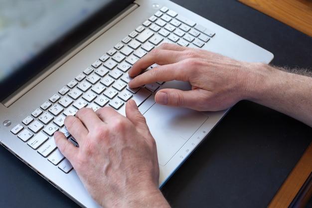 Man handen die op laptop toetsenbord typen. selectieve aandacht