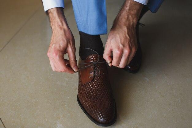 Man handen die schoenveter van zijn nieuwe schoenen binden