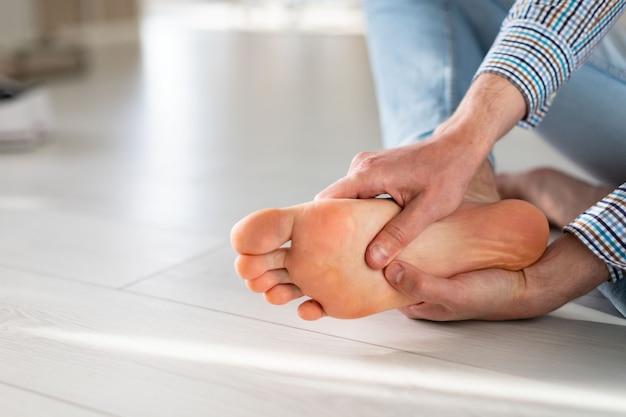 Man handen geven voetmassage aan jezelf om pijn te verlichten na een lange wandeling, vanwege ongemakkelijke schoenen.