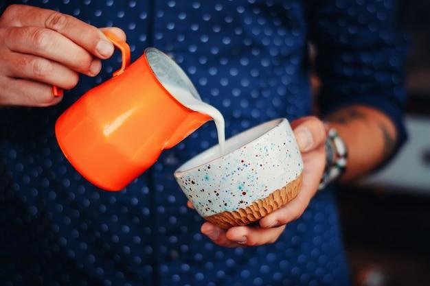 Man handen gieten melk fron werper in koffiekopje, barista cappuccino of latte maken