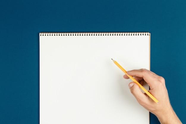 Man handen houden geopende notebookpagina's met potlood, schooljongen huiswerk, bureau van kantoormedewerker plat leggen. lege blocnote op tafel