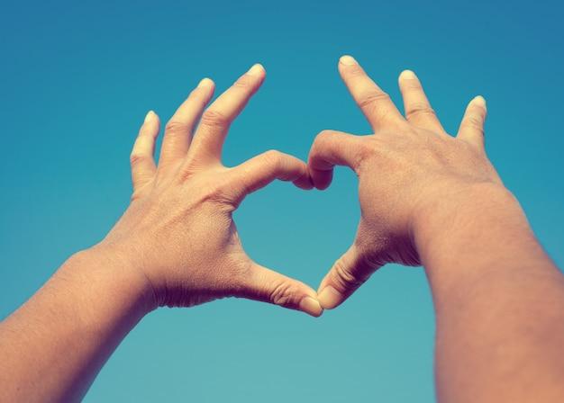 Man handen in hart vorm vorm liefde op de hemel achtergrond, liefde en valentijn concept (vintage kleur toon)