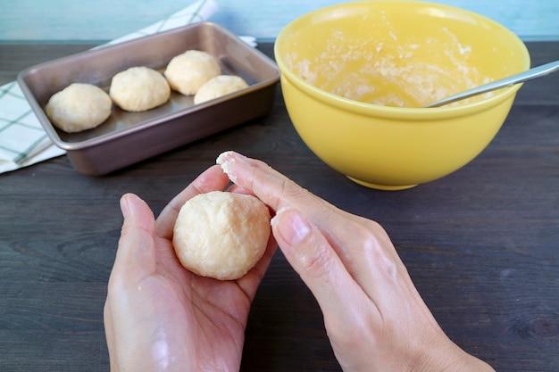 Man handen kneden deeg voor het bakken van braziliaans kaasbrood of pao de queijo