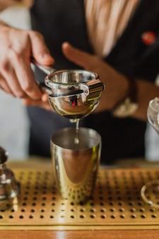 Man handen knijpen limoensap in een shaker aan de bar. selectieve focus, natuurlijk licht.