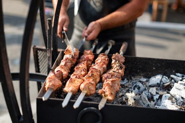 Man handen koken vlees op een barbecue