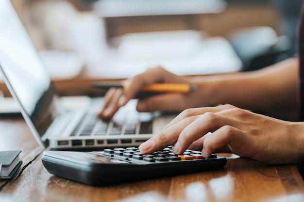 Man handen met behulp van een rekenmachine en laptopcomputer voor het berekenen met financiën papier