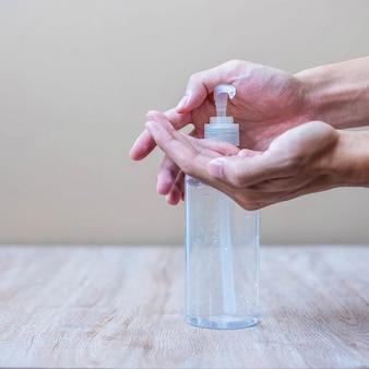 Man handen met behulp van washand alcohol gel of ontsmettingsmiddel fles