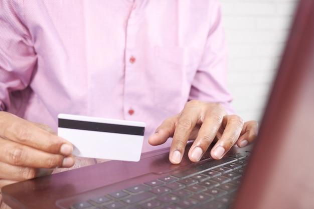 Man handen met creditcard en met behulp van laptop online winkelen