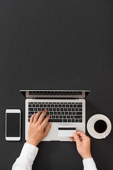 Man handen met een creditcard. laptop gebruiken voor online winkelen, platliggend bureauconcept