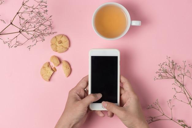 Man handen met mobiele telefoon terwijl hij thee drinkt en haverkoekje eet.