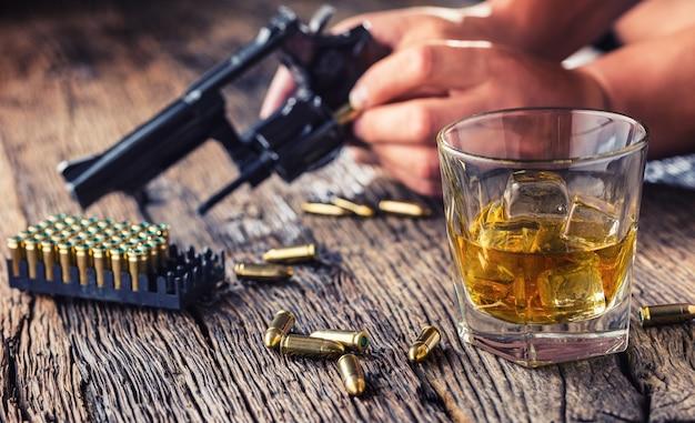 Man handen met pistool en alcohol glas op tafel.