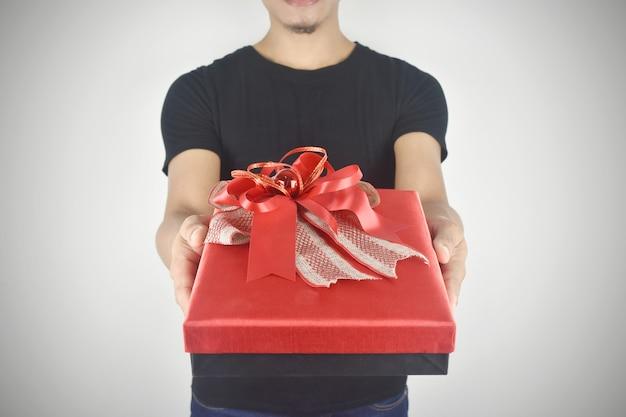Man handen met rode geschenkdoos aanwezig voor verjaardag valentijn dag kerstmis nieuwjaar concept