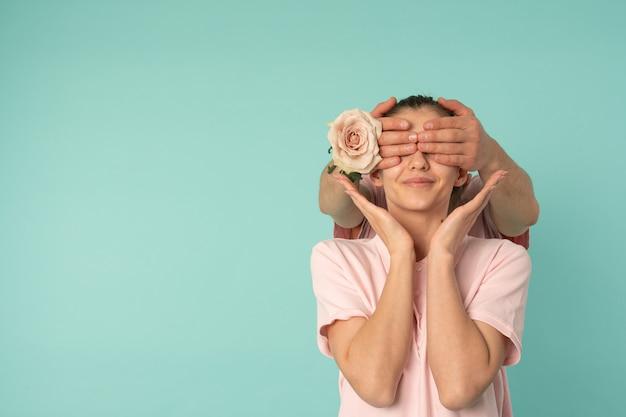 Man handen met roze kegelogen van zijn vriendin, voorbereidend verrassing voor 8 maart, vrouwendag, geïsoleerde moederdag