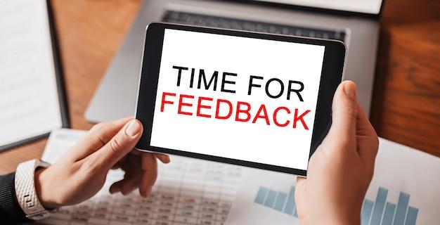Man handen met tablet met tekst tijd voor feedback op de werkplek. zakenman werken aan bureau met documenten