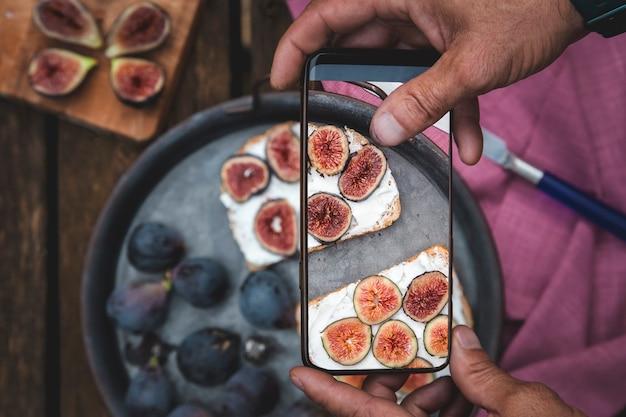 Man handen neemt foto van eten op tafel met de telefoon. ontbijt. sandwich met zachte ricotta en vijgen. smartphone-foto voor sociale media of blogpost. vegetarisch, gezond, biologisch
