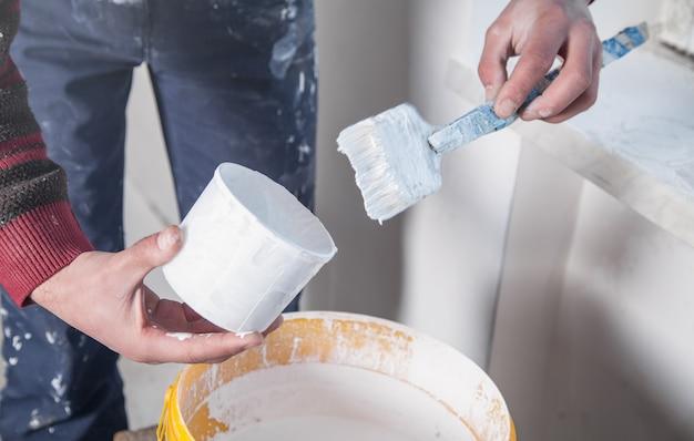 Man handen penseel met witte verf. vernieuwing