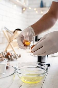 Man handen scheiden dooier en wit van de eierschaal in de keuken