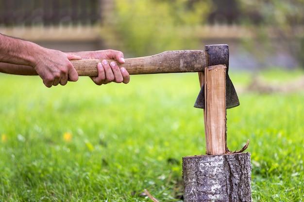 Man handen snijden kofferbak met oude scherpe ijzeren bijl