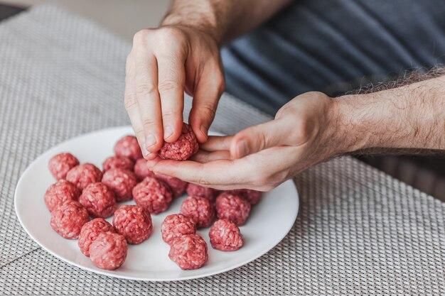 Man handen voorbereiden van gehaktballen met rauw gehakt.