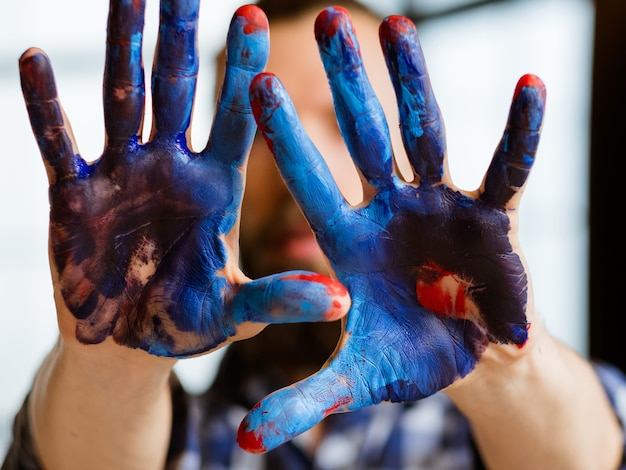 Man handen vuil met blauwe en rode acrylverf.