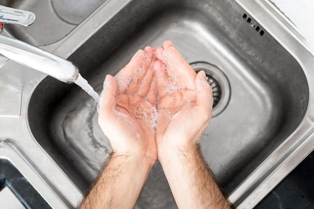 Man handen wassen met water en zeep in metalen gootsteen