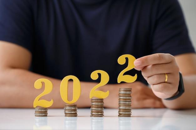 Man handen zetten gouden houten nummer 2022 op stapel munten belastingbetaling investeringen en banking022 n