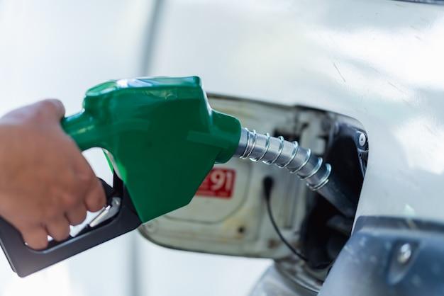 Man handvat pompen benzine brandstof mondstuk om bij te tanken. tankstation voor voertuigen bij tankstation. witte auto bij benzinestation dat met brandstof wordt gevuld. transport- en eigendomsconcept.