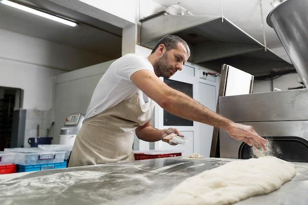 Man hardwerkend in een broodbakkerij