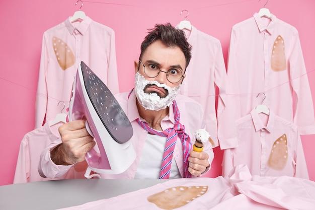 Man heeft aandachtige blik scheert tijdens het strijken jurken voor speciale gelegenheid draagt bril poses tegen gestreken verbrande shirts op hangers geïsoleerd op roze