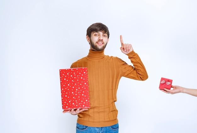 Man heeft een grote rode geschenkdoos en krijgt ook een kleine aangeboden.