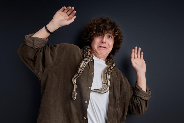 Man heeft een paniekaanval met slang op zijn schouders, verwarde man kan niet bewegen, trekt gek gezicht van angst