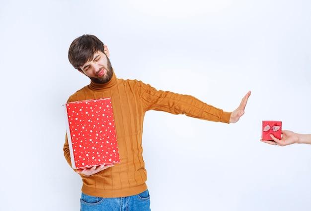 Man heeft een rode geschenkdoos en weigert een andere te nemen.