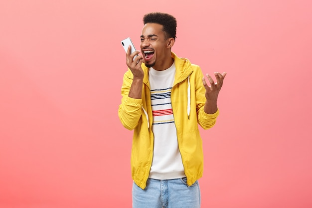 Man heeft genoeg van domme klantenondersteuning die schreeuwt naar smartphonescherm schreeuwend van woedende verontwaardiging gevoelens balde kern met mobiele telefoon in de buurt van gezicht over roze achtergrond