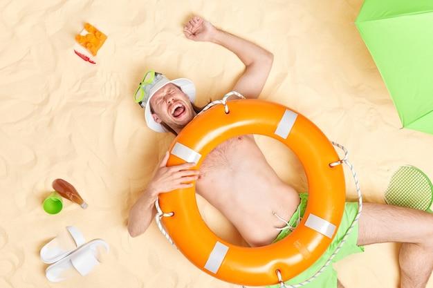 Man heeft plezier ligt op wit zand met opgeblazen oranje reddingsboei op lichaam draagt witte zonnehoed snorkelmasker schreeuwt luid brengt vrije tijd door op het strand tijdens warme zomerdag