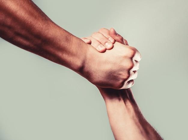 Man help handen, voogdij, bescherming. twee handen, geïsoleerde arm, helpende hand van een vriend. vriendelijke handdruk, vrienden begroeten. redding, helpende hand. mannenhand verenigd in handdruk.