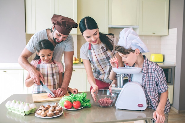 Man helpt haar dochter om vlees te snijden met mes. zoon stopt een stukje ervan in de vleesmolen. moeder kijkt ernaar en houdt de kom met beide handen vast.