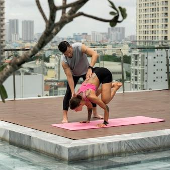 Man helpt vrouw yoga bij het zwembad