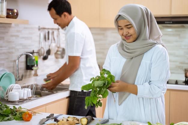 Man helpt zijn vrouw in de keuken. moslim aziatisch paar dat diner samen voorbereidt. romantische jonge man en vrouw hebben plezier bij het maken van eten thuis